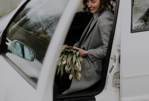 Woman getting out of a car with flowers