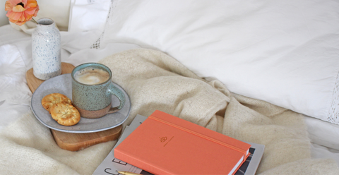 Image of Ponderlily planner on bed with coffee