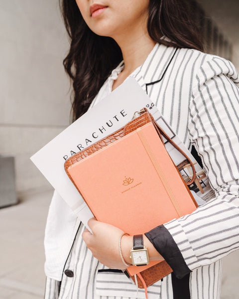 Woman in striped blazer holding a pink Ponderlily Weekly Planner