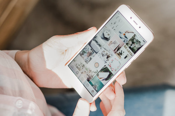 Create positive change to your social media scrolling habit by following these productivity experts on Instagram - phone shows beautiful Instagram grid