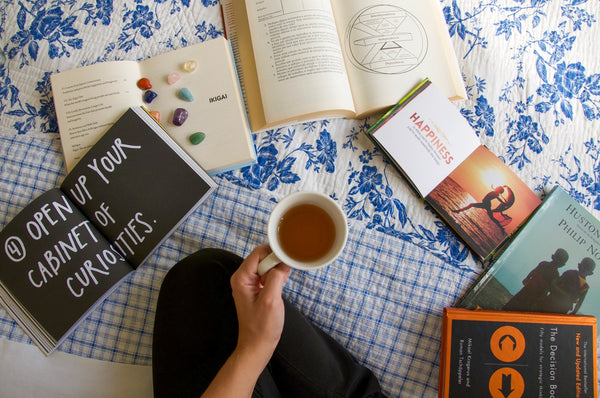 woman holding a cup of tea with a variety of gratitude books open on the floor