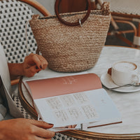 Woman reading inspirational quotes and notes from daily planner while sitting at outdoor cafe with her purse and cappuccino