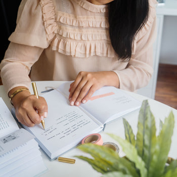 Picture of woman writing with brass pen on a Ponderlily planner