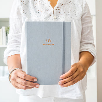 Woman holding the Warm Gray Ponderlily weekly planner