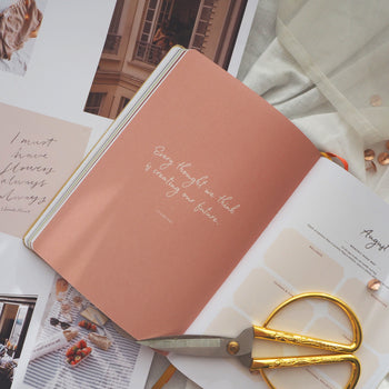 Gold handle scissors atop planner opened to page with inspirational quote