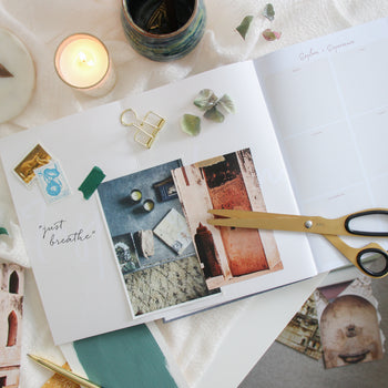 Inspiration and vision board in the Ponderlily planner with candles and scissors near