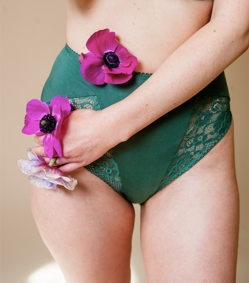 Woman wears green lace underwear and holds flowers near her abdomen