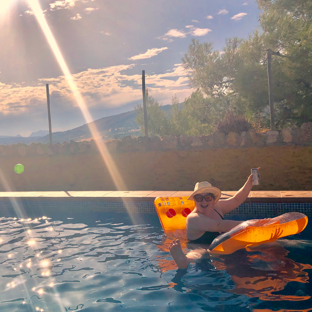 Joeley waves from a pool floatie in a swimming pool