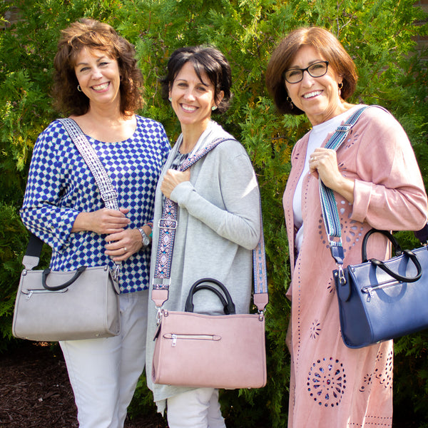Founder of the New Day Foundation, Gina, with two members of her team; all wearing the Gina Satchel.