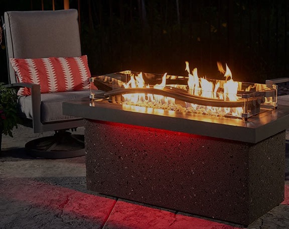 A unique fire pit sits with a highback chair in a backyard