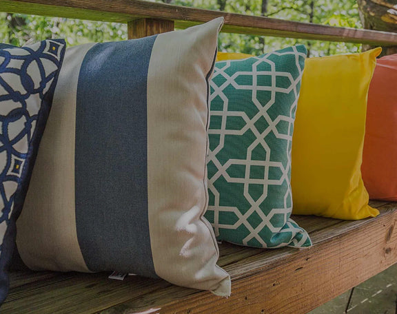 A row of colorful pillows adorns a wodden banch outdoors.