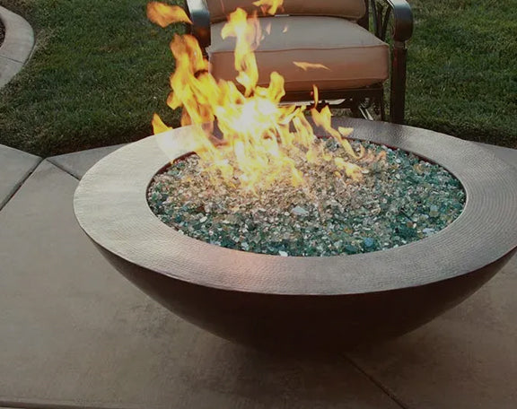 Copper fire bowl is ignited in a backyard setting