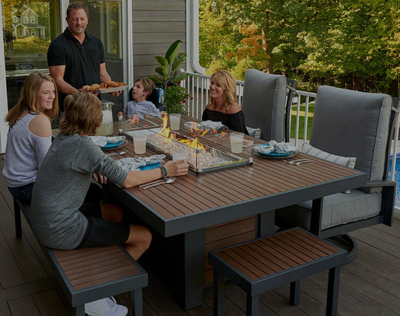 A family of 5 sits outdoor at a fire pit table with fire glass and glass surround in their backyard.