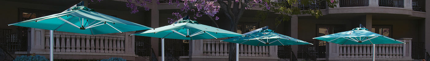 four square hotel patio umbrellas are in a resort courtyard.