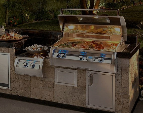A complete outdoor kitchen grilling setup is displayed with lit interior hood
