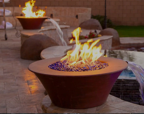 beautiful ceramic fire bowls pour water into a pool at sunset