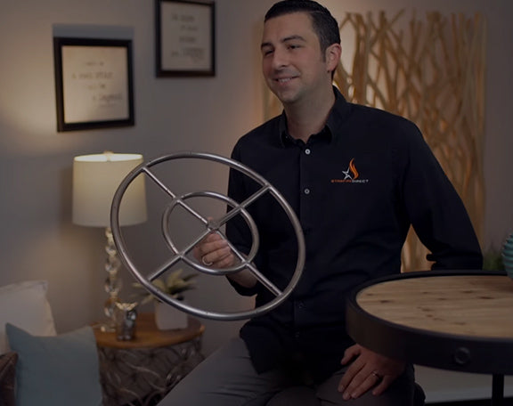 A Starfire Direct professional is talking about the gas igntion burner in his hands as he smiles