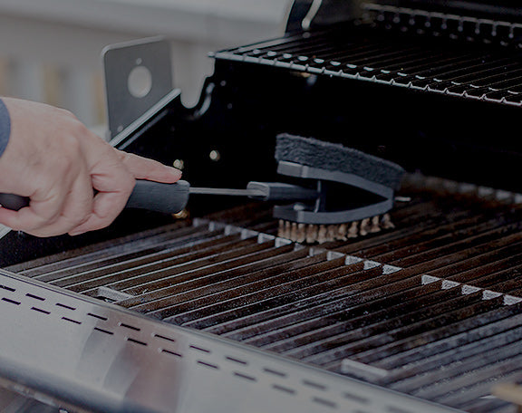 a specialized grill scraper is used to clean the inside of a grill