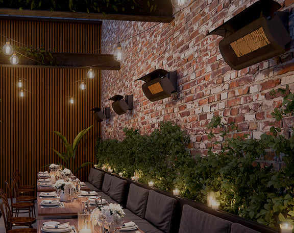 A set of overhanging wall heaters heat up an outdoor dining area