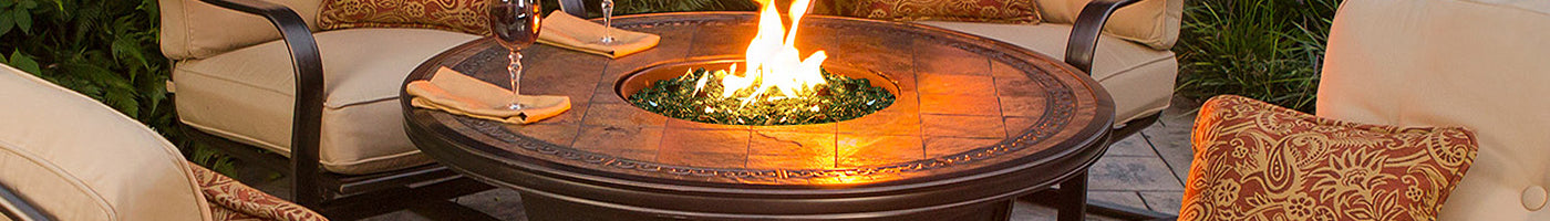 A fire pit table sits in a beautiful backyard