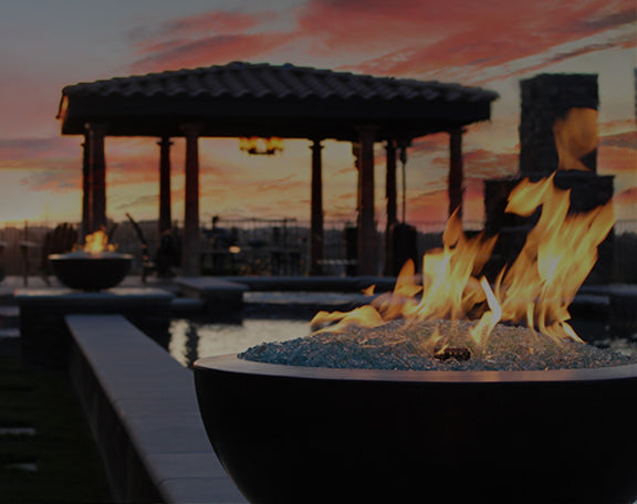 A set of fire bowls are aglow next to a pool at sunset