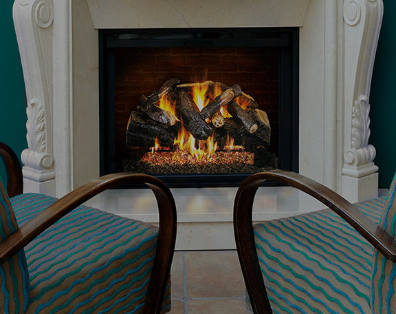 A stunning gas log set sits in a modern fireplace in front of two chairs.