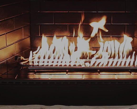 A fireplace is empty except for a gas H-burner
