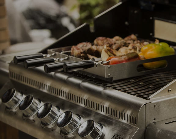 A specialized grill skewer tool is being used on a high end gas grill to barbecue some kabobs