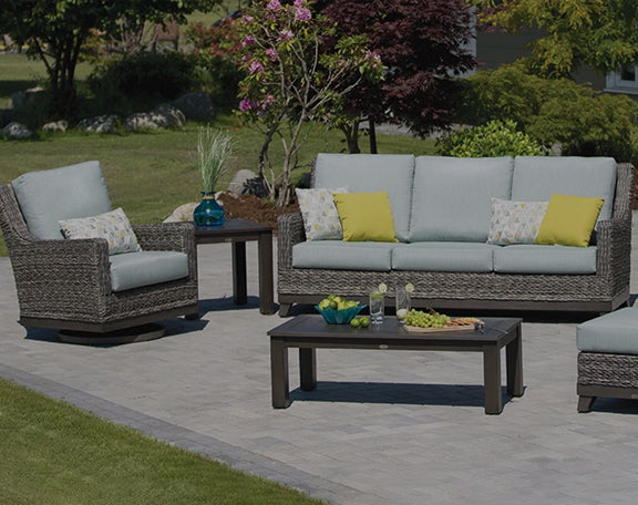 A wicker style patio set is displayed in a sunny backyard.