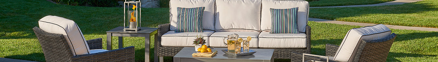 A stunning wicker patio set is ready for guests at sunset with lemonade and a tabletop heater