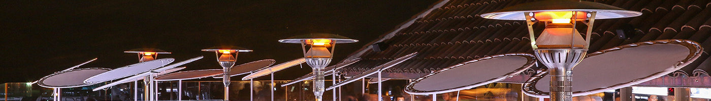 Several inground post heaters are warming up a hotel patio at night.