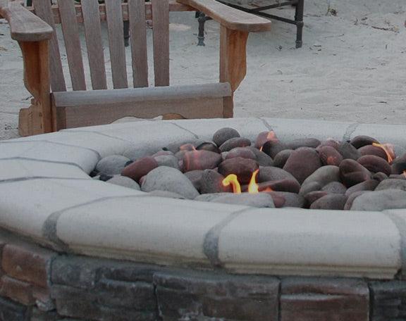 A DIY fire pit is barely ignited as it sits in a beach setting