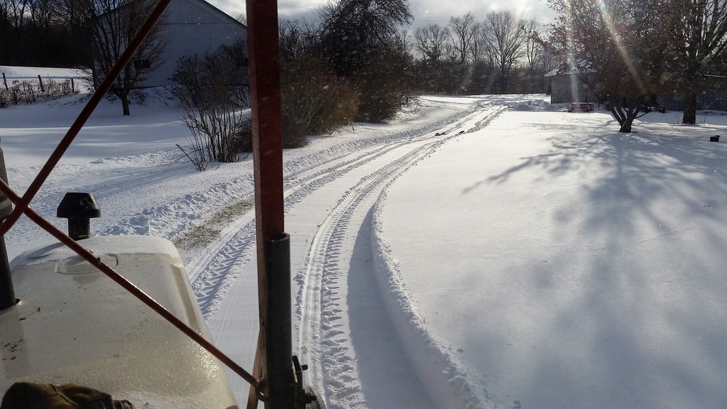 Driveway cleared with snowblower on tractor