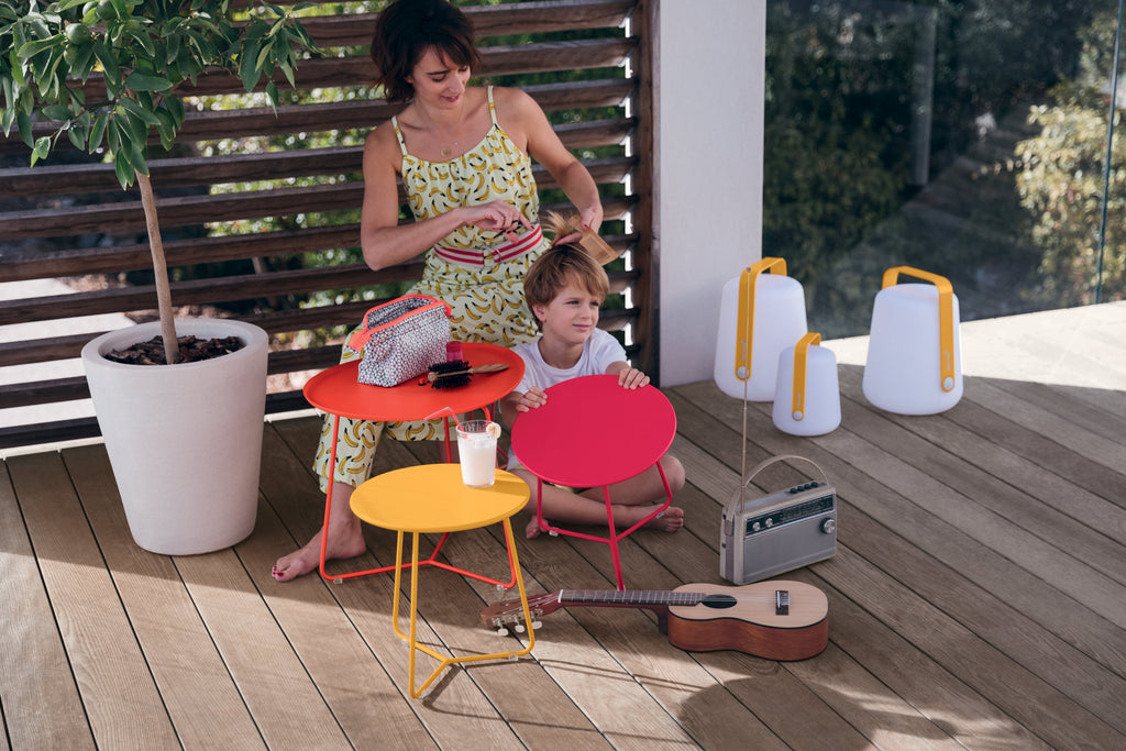 Fermob Cocotte Tables in Bright Colours with a Mum and Son playing next to them