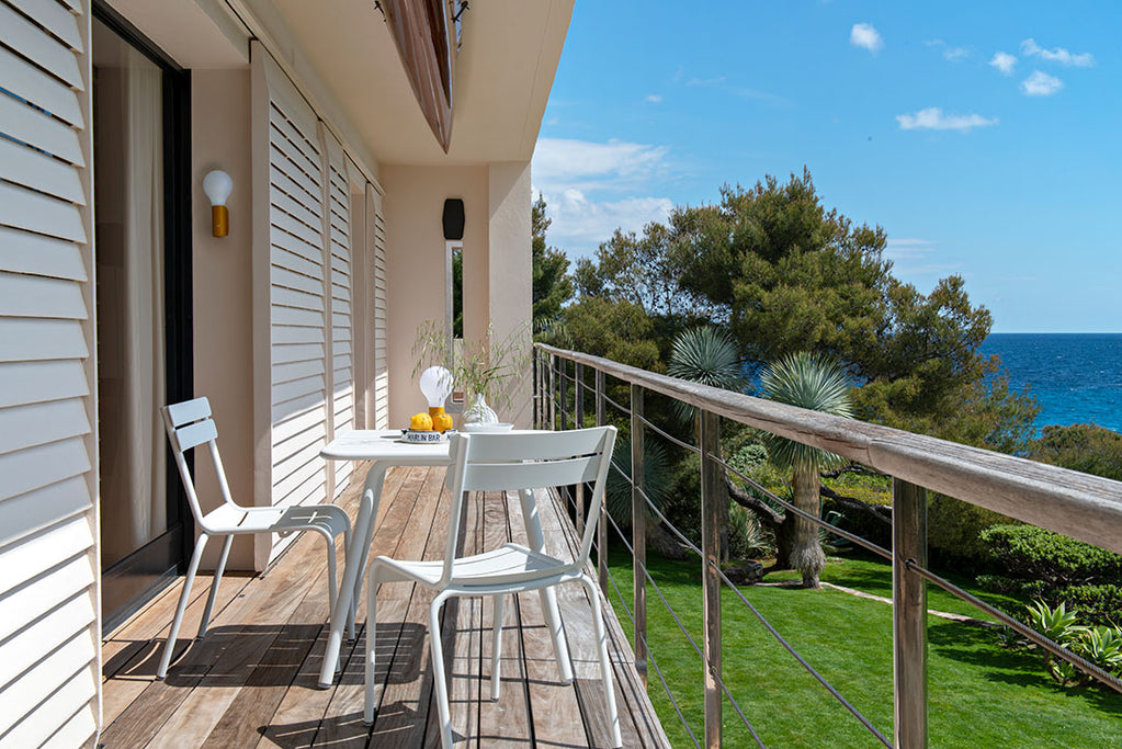 Fermob Luxembourg Chairs and a Bistro Folding Table, all in Poppy Red, pictured on high apartment Patio