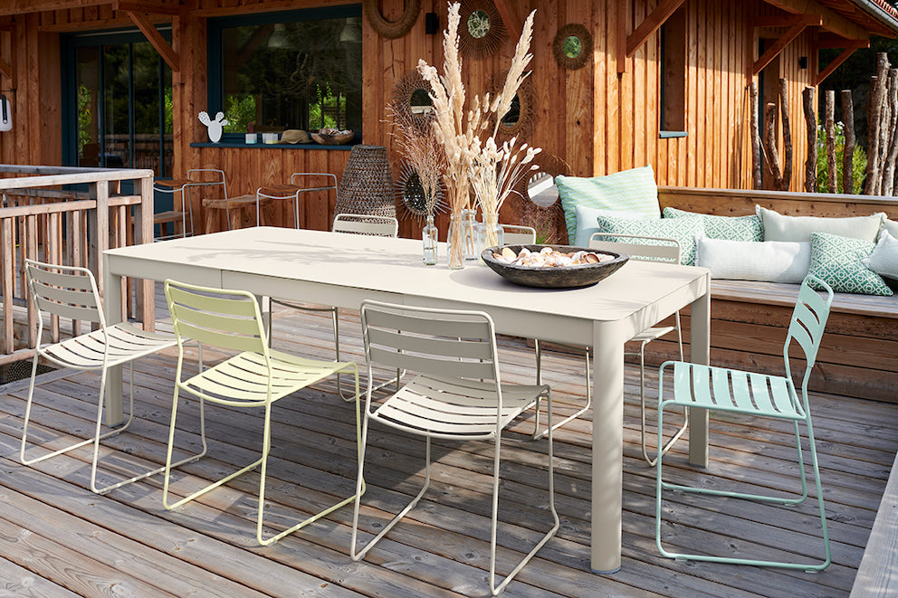 FERMOB Surprising Chairs on pastel colours around a Ribambelle Table, all set on wooden decking