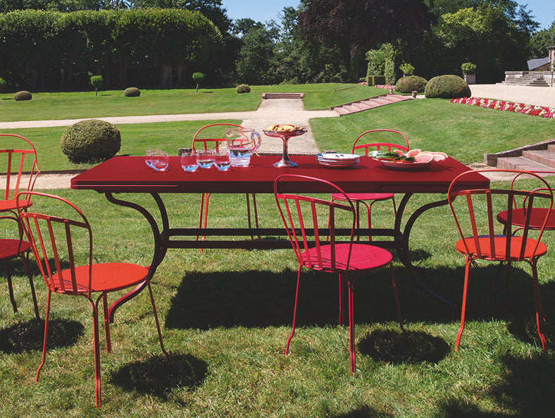 Red Fermob Louvre Chairs Romane Table, on a large garden lawn bathed in sunshine