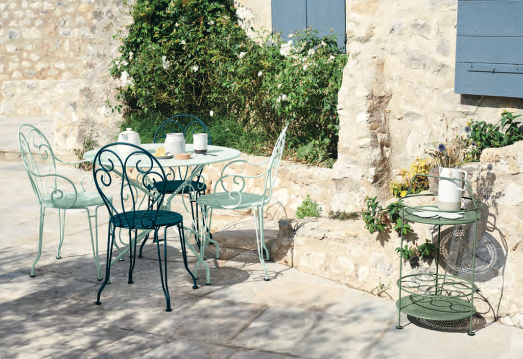 A sunny courtyard setting of Fermob Monmartre Table and Chairs