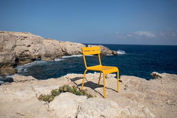 A honey Luxembourg Chair designed by Frederic Sofia for Fermob, sitting on rocks with the blue sea behind.