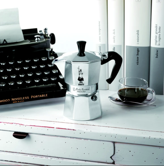Bialetti Coffee Maker. Classic Italian Moka Express Maker.  Pictured next to a typewriter and Glass cup.  Sophisticated and Stylish!