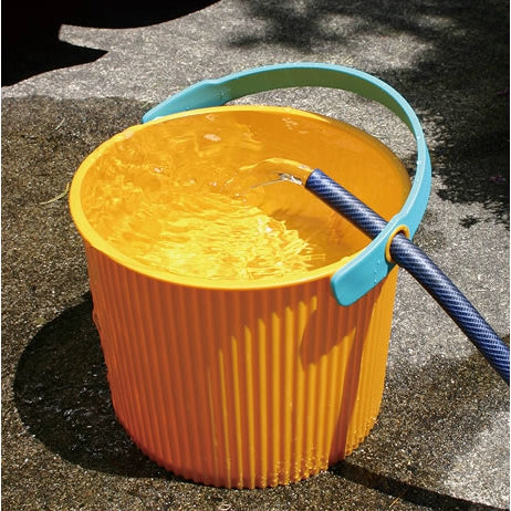 Hachiman Omnioutil Bucket in Yellow being filled of water through a hose.