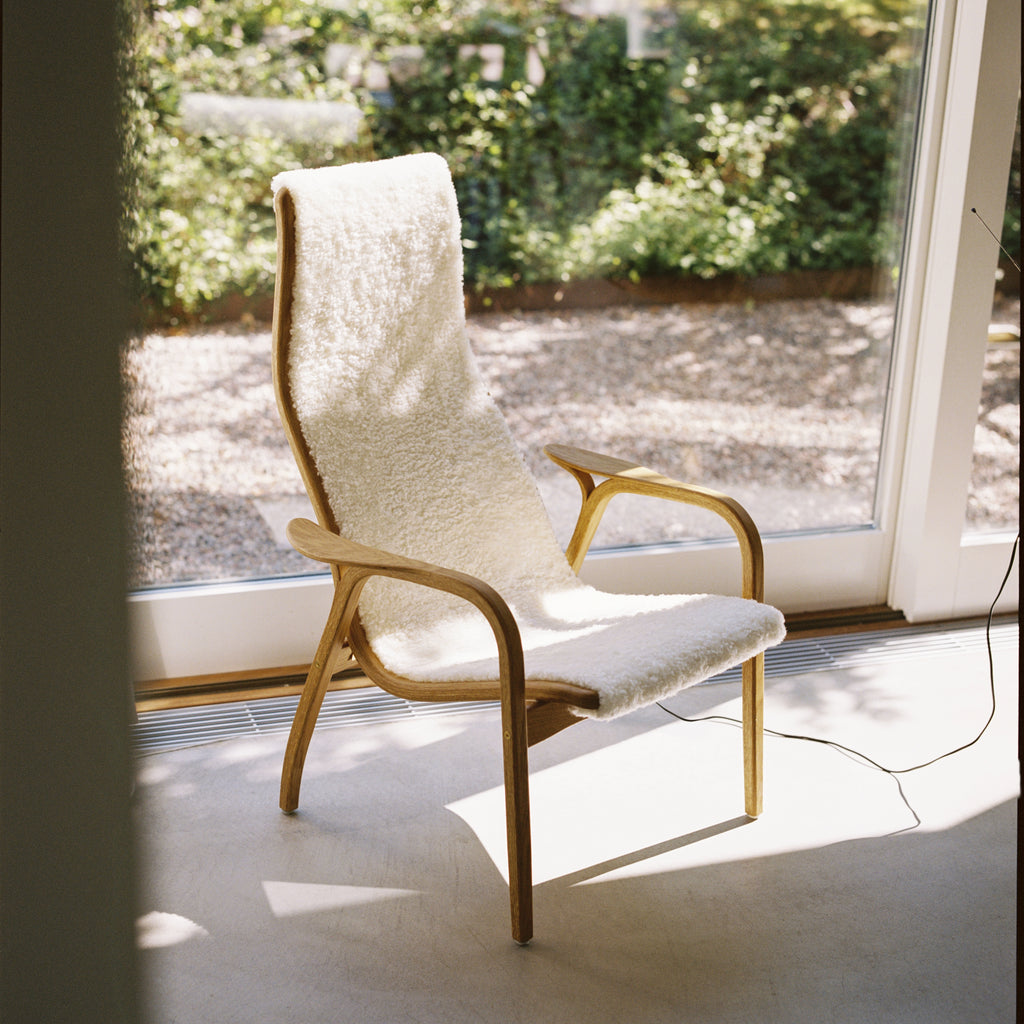 Yngve Ekstrom's Lamino Chair with White sheepskin in a sunny spot next to a big window