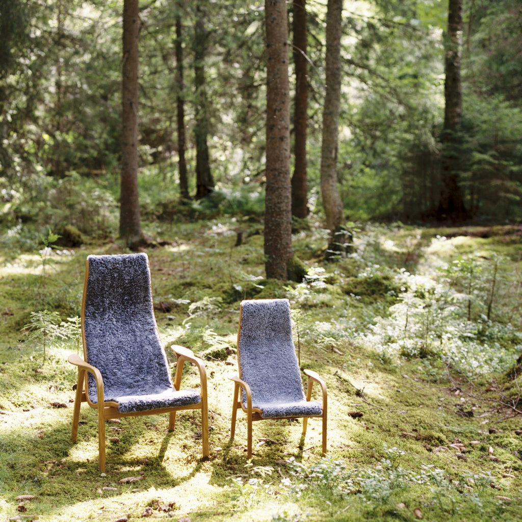 Lamino Chair in woodland setting next to a smaller Lamini chair with sunlight beaming down onto the chairs.