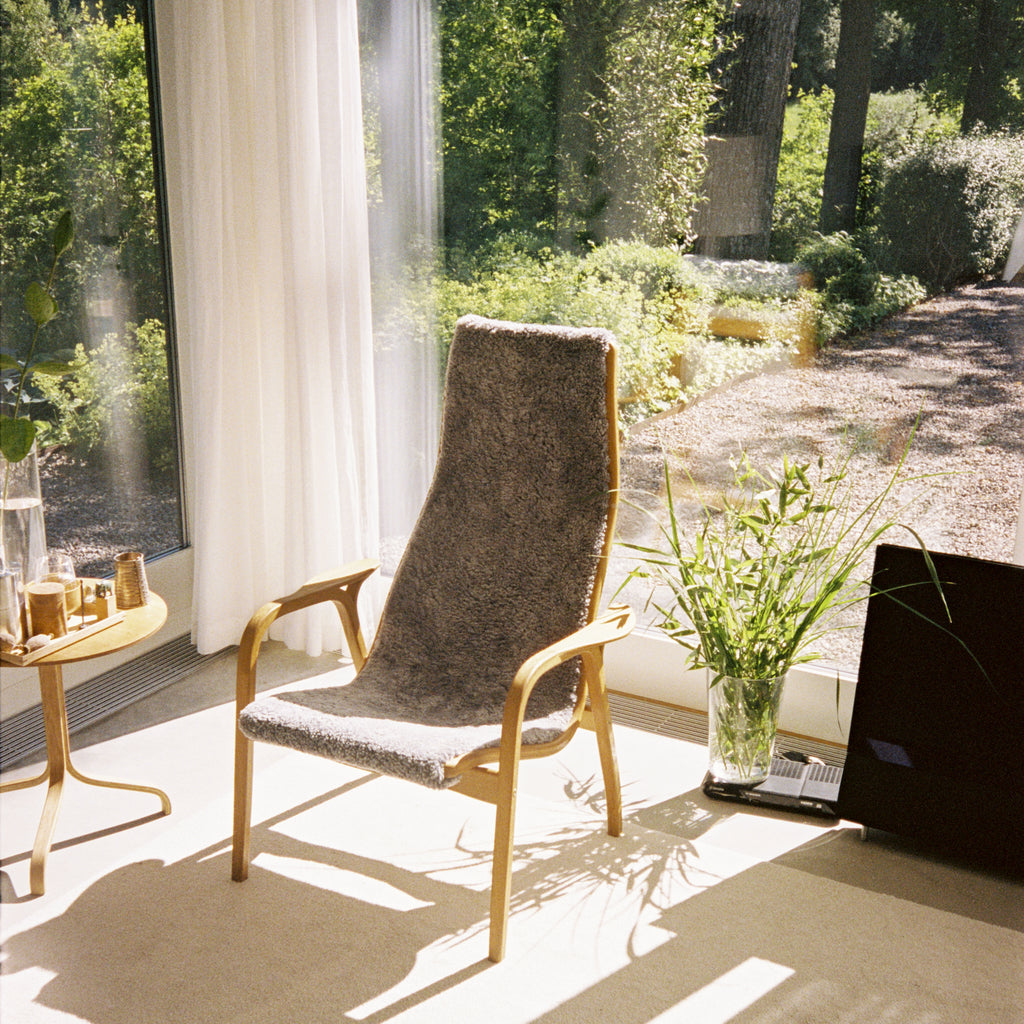 Yngve Ekstrom's Lamino Chair in the corner of a room with big windows and sunshine flooding in