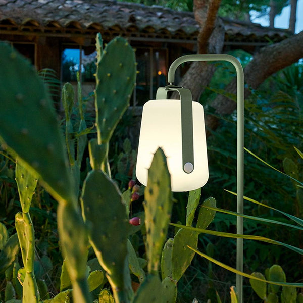 Fermob Balad Spike Stand in Cactus with a Fermob Balad Lamp in Cactus attached in a green garden setting outside a wooden Cabin.