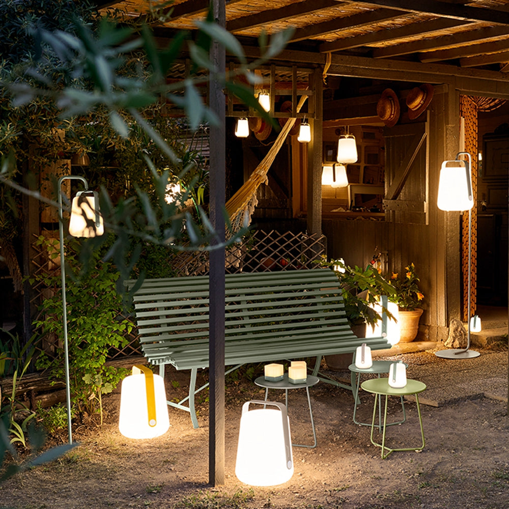Fermob's Balad Lamps and Balad Upright stands next to a bench and Wooden Cabin.