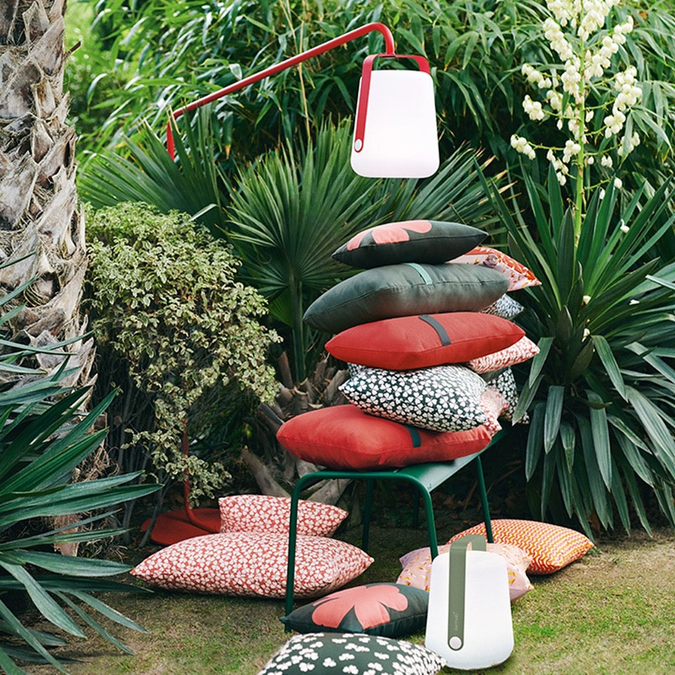 Fermob Balad Offset Stand with Lamp attached above pillows stacked onto of each other in a Green Garden setting.