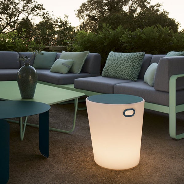 Fermob Inouï Lighting Stool in Acapulco Blue glowing next to a green table and two sofas.