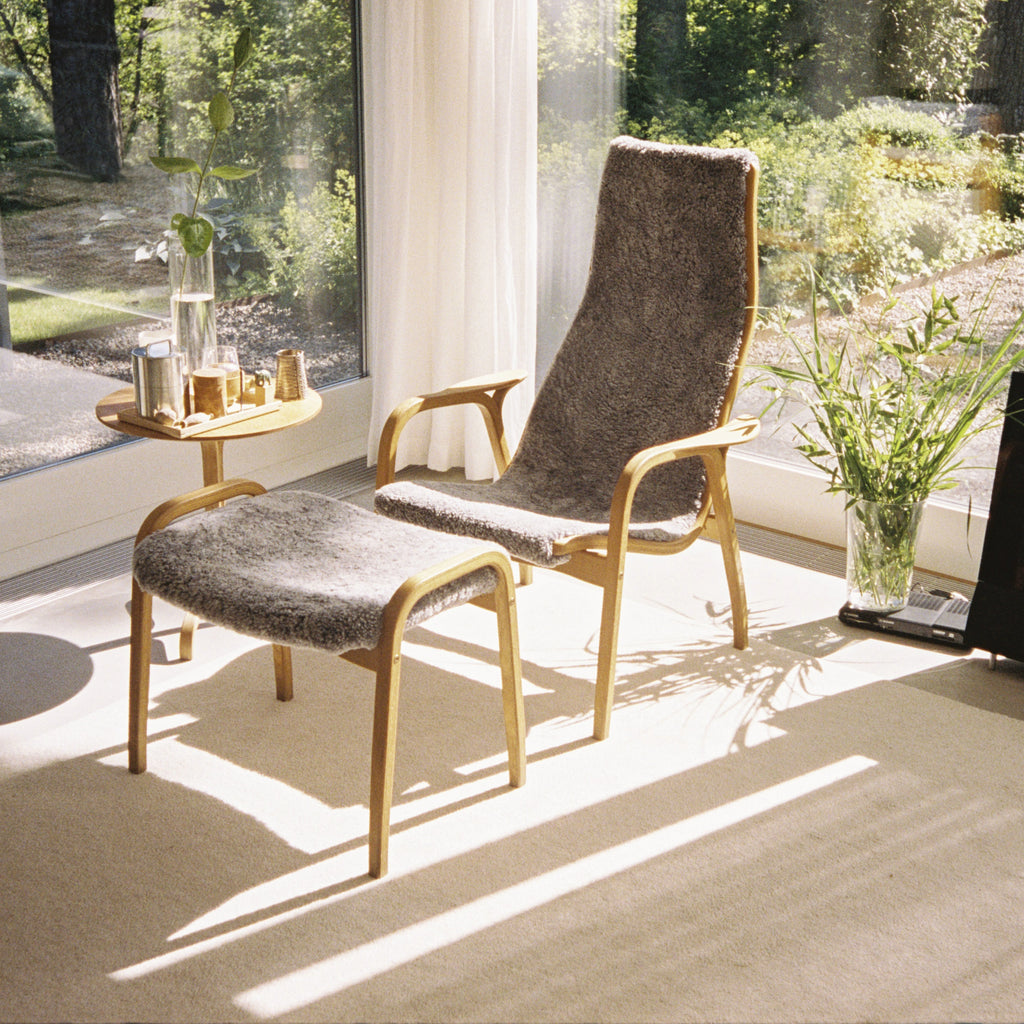 Yngve Ekstrom's Lamino Chair and Footstool next to big windows with sunshine flooding in