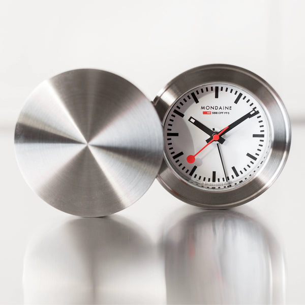 Front and back angle of a Mondaine Swiss Railway Travel Alarm clock with a 50mm Diameter and Silver frame.